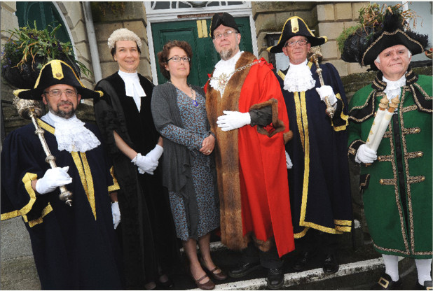 Glastonbury's 317th Mayor, Green Councillor Jon Cousins with: (left to right) Macebearer Gary Day, Town Clerk Jane Czornij, Mayoress Lucia Forge, the Mayor, Macebearer Gary Knight, Town Crier David Greenway.